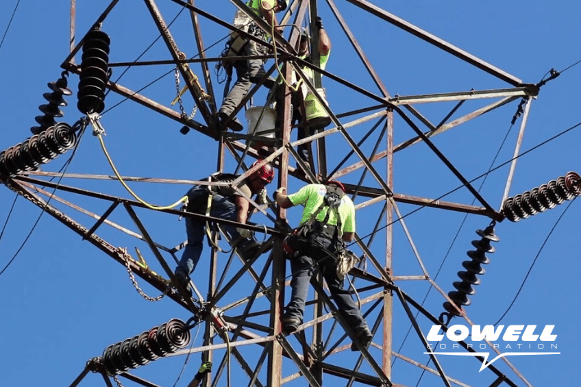Group of transmission lineman performing electrical work on a transmission tower.